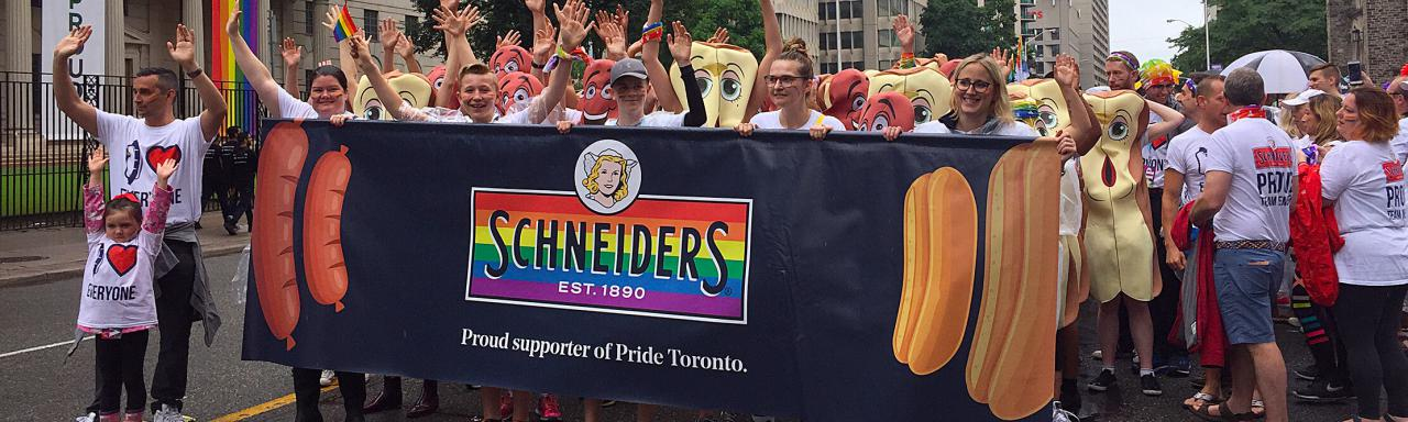 Employees marching in Pride Toronto parade holding Schneiders banner displaying pride colours.