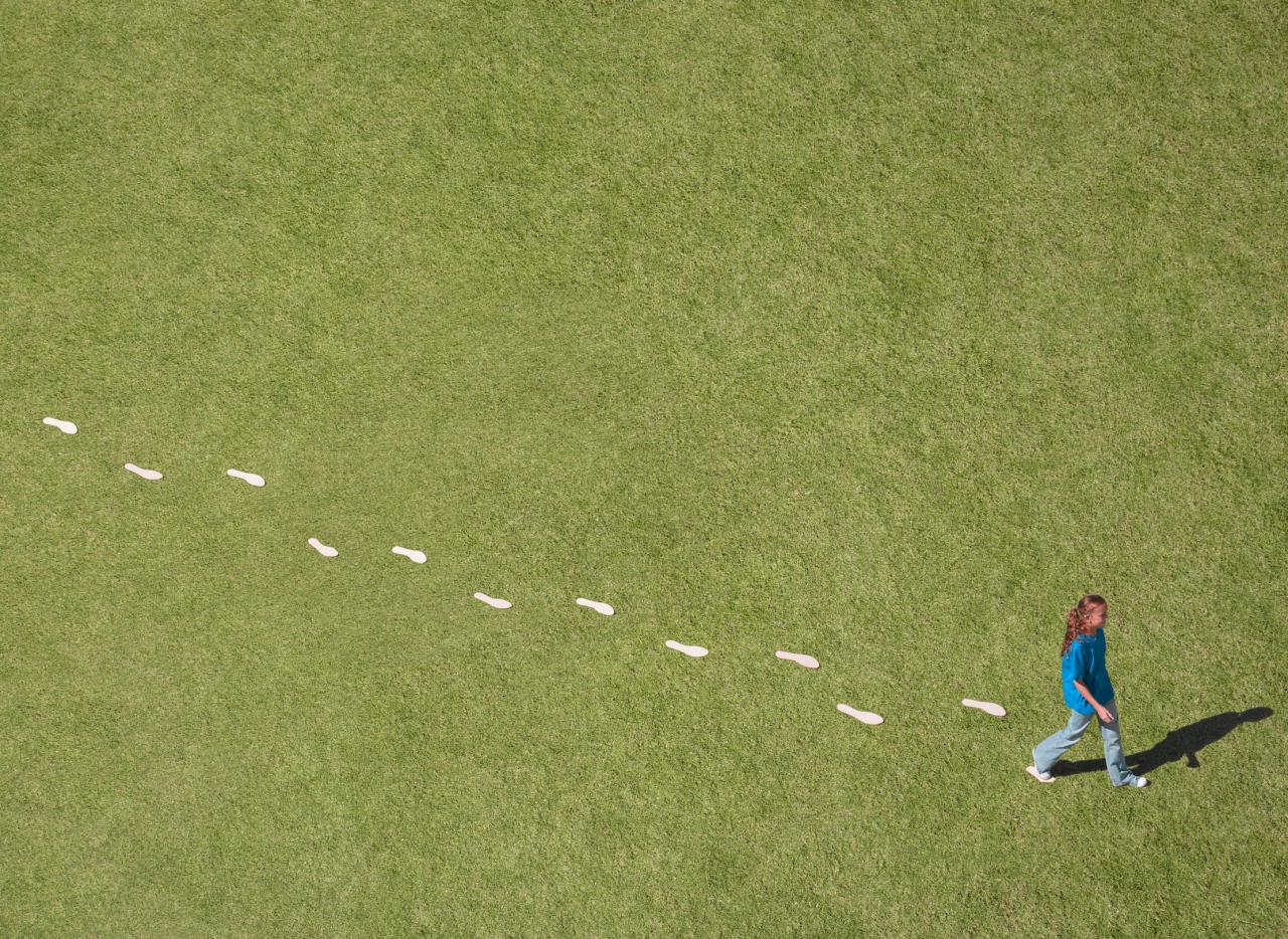Woman walking on green grass with white footprints behind.