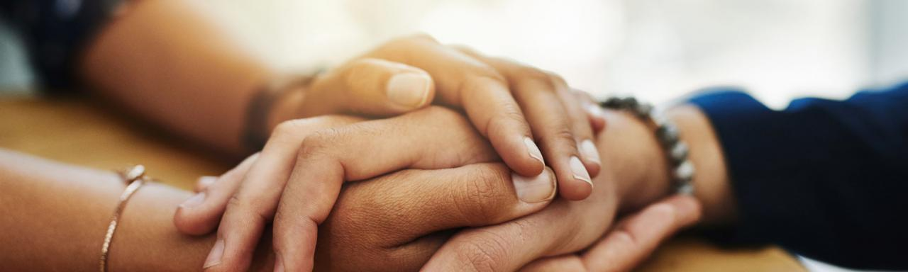 Closeup of two people holding hands in comfort.